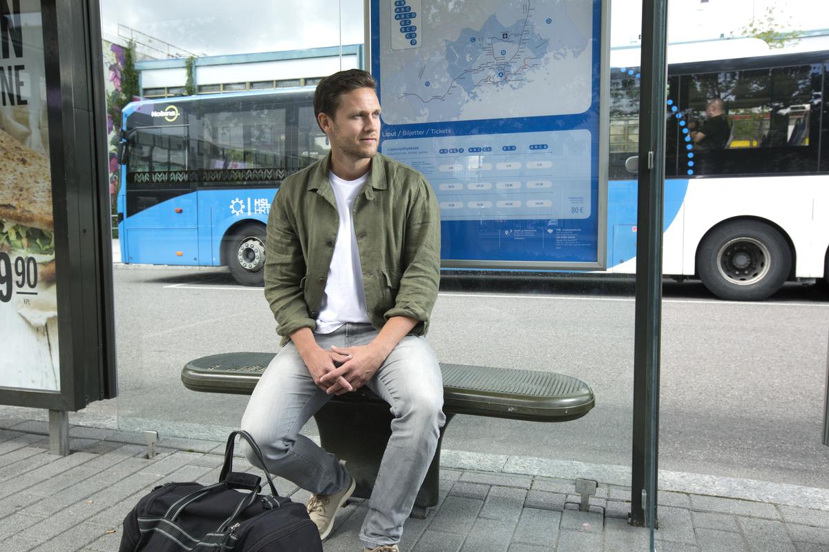 Mies istuu bussipysäkillä, laukku jalkojen edessä ja bussi taustalla.